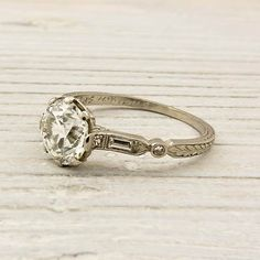 White gold, organic style engagement ring with round brilliant diamond center stone and baguette accents. I like the ornate bands of  vintage rings.
