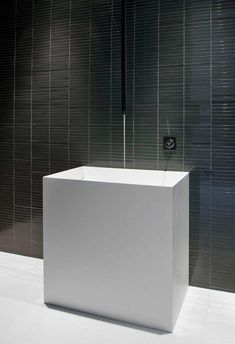 Minimal white washbasin combined with grey wall inside the Glass Pavilion in Santa Barbara by Steve Hermann _