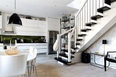 Kök med gott om förvaring bakom skåpsluckor i dubbla rader och bra arbetsytor på bänkskiva av blankpolerad svart skiffer.. KÖKSLUCKA: Line vit/alu | Ballingslöv