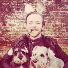 Simon Pegg wearing bunny ears, smoking a pipe and hanging with some pups.