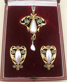 An Art Nouveau gold pendant with matching clips, by Lucien Falize, circa1895. The pendant collet set with green stones, rose diamonds and a Mississippi pearl, suspending a further pearl, the clips, similarly set with mother of pearl centres, with an additional pair of hinged brooch fittings enabling the pair of smaller jewels to be worn as hair ornaments or more conventionally brooches. In a red leather fitted case by Falize, 6 Rue d'Antin, Paris. With French assay marks and maker's mark.