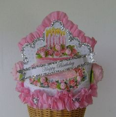 """GH """"Happy Birthday"""" cake Crown - Glam Hatter Birthday Crown - Hat has a sturdy cardboard base covered in tiny Lt. blue dot paper. Trimmed with my handmade crepe paper ruffles and roses and lots of old fashioned glitter!  Front has glittered vintage birthday cake with my tiny roses and banner that says """"HAPPY BIRTHDAY""""!  Adjustable to fit any size child or adult with my signature muslin ties. Birthday Cake Crown, Vintage Birthday Cakes, Birthday Party Hats, Happy Birthday Cakes, Brown Paper Packages, Crepe Paper, Birthdays, Crafty, Crowns"""
