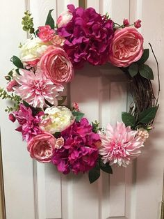 This is a very colorful wreath full of purple, pink, and white flowers with small roses and green leaves. It features hydrangeas and peonies. It is on an 18 inch grapevine wreath. This will draw the attention of others and make a wall or door shine