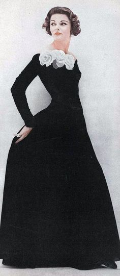 Model is wearing a black velvet gown with a curve of silk roses by Sophie Original, jewelry by Harry Winston, photo by Karen Radkai, Vogue Sept. 1956