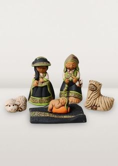 Mary and Joseph, wearing traditional Peruvian garb, gaze lovingly at the Christ child while two resting animals look on.
