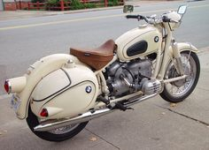 White vintage BMW with hard bags and  solo saddle.