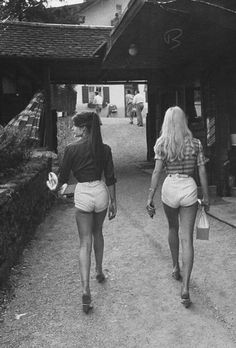 Unknown brunette and blonde hotties walking down a small little street.