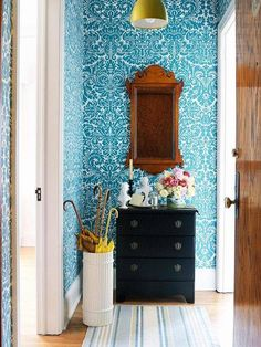 Traditional entryway with a vibrant blue wallpaper, a gold sconce, and a vintage mirror