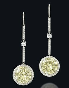 A PAIR OF COLOURED DIAMOND AND DIAMOND EAR PENDANTS  Each designed as a cluster drop composed of a brilliant-cut fancy yellow diamond centre, weighing 4.97 and 5.05 carats respectively, within a circular-cut diamond line surround to a similarly-set bar surmount, 5.2cm long, diamond-set hook fittings