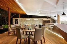Nosotros Bar avec des tables rondes en bois, chaises tapissées grises et un meuble bar design en bois