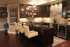 An incredible contemporary luxury home bar with glass-faced cabinetry, a beverage cooler, and a two-tier bar area in granite. The textured stone backsplash is an incredible detail.