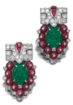 A pair of Art Deco ruby, emerald and diamond clips, Cartier, 1930s. Each clip…