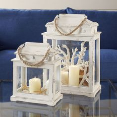Brimming with beach-chic appeal, this wood and glass lantern set showcases coastal accents and rope handles.