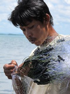 A Moken Sea Gypsy fisherman tends to his net. #Thailand