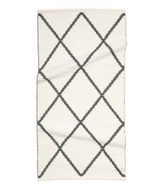 White/Patterned. Rectangular cotton rug with a jacquard-weave pattern.