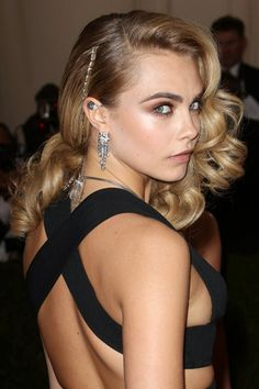 Cara Delevingne wore her hair curled and swept dramatically to one side with a jeweled accessory, whilst her make-up look comprised smoky eyes and nude, matt lips. Met Gala 2014