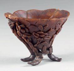 COUPE LIBATOIRE quadripode en forme de feuille de lotus en corne de rhinocéros à décor sculpté en relief et détaché de pivoines dans leur feuillage. Chine, XVIIe/XVIIIe siècle. (Petite restauration à un pied et éclats). Hauteur: 9,5 cm - Longueur: 12 cm Poids: 180 g