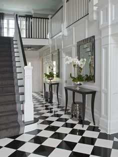 Chic foyer with silver stools tucked under black console tables paired with rectangular mirrors over black and white checkered tiled floor.