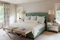 A green upholstered bed makes a splash of color in the serene sea of neutrals of this traditional bedroom. Simple metal and leather stools at the foot of the bed double as end tables.