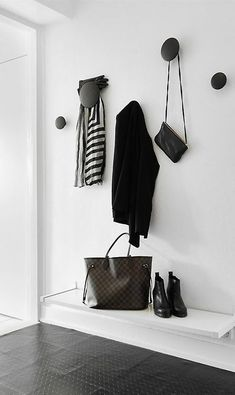 20 things to hang on walls - from domino,com: black hooks against white wall by front door because there isn't full entry (I.e., no coat closet)