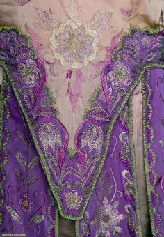 "THREE JEWELED SILK DRESSES, 1925-1934 2 mid 1920s beaded flapper dresses: 1 turquoise, aqua, seafoam green & silver beading, fair; 1 pink & magenta embroidered & beaded dress, label ""Eugenie et Juliette Paris"", poor; 1 early-mid 1930s purple, pearl & rhinestone studded pearl & rhinestone studded bodice, fair, all fragile. Detaile"