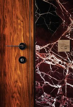 Deep red marble, brass light switch & warm wood. Dramatically veined red lepanto marble on the walls in the Italian hotel Palazzo Fendi / interior style