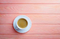 coffee cup and beans on a pink wood background