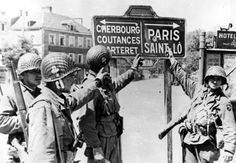 Four paratroopers of the 101st Airborne Division at a road sign in the town of Carentan, 1944. #WW2