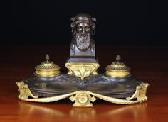 A Bronze French Empire Desk Set. The brown patinated tray ornamented with sprays of stylised flowers flanking a pen trough, and mounted with the bust of a classical scholar to the back with gilded inkpot and ponce holders either side. The tray raised on gilded feet and adorned with a gilt swag, 9½ in (24 cm) high, 15 in (38 cm) wide.