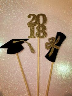 Celebrate your graduates accomplishment with custom centerpieces matching their school colors! This listing is for 1 centerpiece which includes 3 toppers One Diploma, One 2018 and One Graduate Hat all made from beautiful card stock. They are attached to food safe bamboo skewers that are