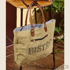 Pre-order now! The Bistro Canvas Tote features khaki colored tarp with faux leather handles and a printed graphic on one side, front zipper pocket.