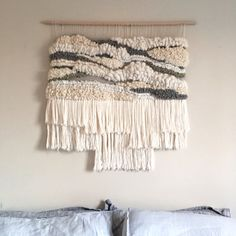 This is a one of a kind woven wall hanging made of all natural wools and fabrics. The piece hangs on a wooden rod which is easily hung on a wall with a simple nail. At its widest point the weaving is 30 wide, and 32 long at its longest point of fringe. This item is available for shipping and looks amazing over a bed, a couch, or in a dining room
