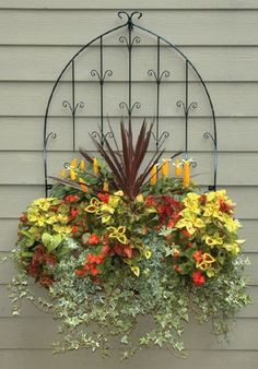 Transform bare walls with Pamela Crawford's side planting Window Box and our ornate Wall Trellis combination.... This would look simply smashing on the brick wall by the front door, playing into both the arched window frames and the Spanish style.