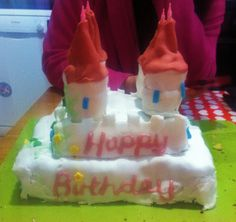 Castle birthday cake, made from brownie and cookie square bricks and cupcake turrets