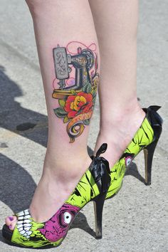Pretty rose and Singer type sewing machine tattoo, accessorized with Iron Fist zombie spikes. From NIX , the Toronto tattoo convention.