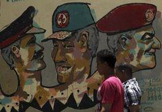 Dos transeúntes, ante un grafiti de miembros de la Junta Militar, en El Cairo. / AMR ABDALLAH DALSH (REUTERS)