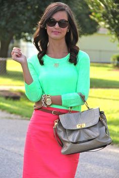 Neon scoopneck sweater, bright pink belted pencil skirt, metallic grey satchel, and gold stacked jewelry.