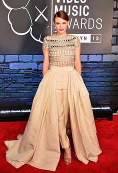 "Holland Roden wearing Naeem Khan with the unique ""ball skirt over cigarette pants"" look. The champagne colored piece features a silver mirror beaded top. She completed it well by working a bold red lip, smoothing her red hair into a chic chignon, and finishing it with Rupert Sanderson peep-toes."
