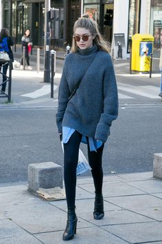 Gigi Hadid in black leggings, black booties, a chambray shirt, and a gray sweater.
