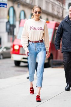 """March 20, 2018 Hadid's """"Pina Colada"""" top by PLNY LaLa served as the ultimate reminder to book that beach vacation. She wore the long-sleeve shirt with cropped Sandro jeans and NewbarK red velvet slippers."""