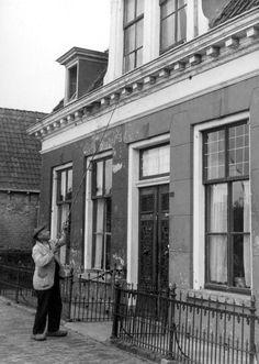 Wekservice uit vroeger jaren: een porder / 'wekker' tikt met zijn porstok tegen een slaapkamerraam in Leeuwarden, 1947.
