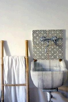 a small square of tiles brings life to this otherwise simple bathroom Laundry In Bathroom, Small Bathroom, Washroom, Morrocan Floor Tiles, White Heaven, Outdoor Sinks, Old School House, Moroccan Design, White Decor