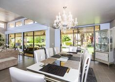 Gorgeous dining room lit by chandelier and abundant natural light - Turnkey Vacation Rental Palm Springs Vacation Rentals, Dining Room Lighting, Hollywood Glamour, View Photos, Natural Light, Chandelier, Modern, Table, Furniture