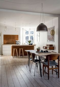 Lovely, warm and open kitchen with brown leather on the fronts of the kitchen island and a massive copper plate on the wall.
