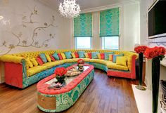 Beautifully eccentric, bright decor, just so much to love, the chandeliers, the turquoise damask patterned blinds. This luxurious over the top couch in yellow salmon and turquoise, it burns my eyes yet I cannot look away!