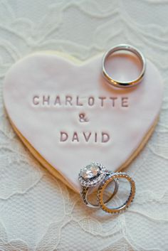 I wanna do this for my wedding/engagement. Heart sugar cookie with names engraved on it and wedding rings on top.