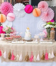 Fun dessert / cake table backdrop with paper flowers and globes and hanging fringe. I like the color combos of orange shades of pink and tan. #MerryBrides