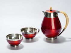 Art Deco : This tea set is comprised of a tea pot, a milk can and a sugar bowl. It was made by the Norwegian silversmith David Andersen. All pieces are made of 925 silver and luminous red enamel. The elegantly curved handles and the nub on the lid are made of ivory which carries a honey-coloured patina. The edges are decorated with a floral vine.