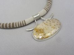 By Linda Magi - Center Coil Necklace with Leopard Skin Jasper.   Argentium sterling silver, hand crocheted pearl cotton and leopard skin jasper stone.