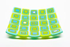 Lots of colored squares and rectangles of hand cut glass layered on top of each…
